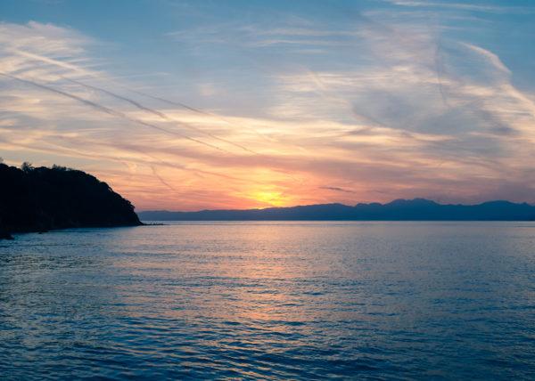 Vue panoramique d'Enoshima, de sa mer, et de son soleil couchant révélant la silouhette du Mont-Fuji