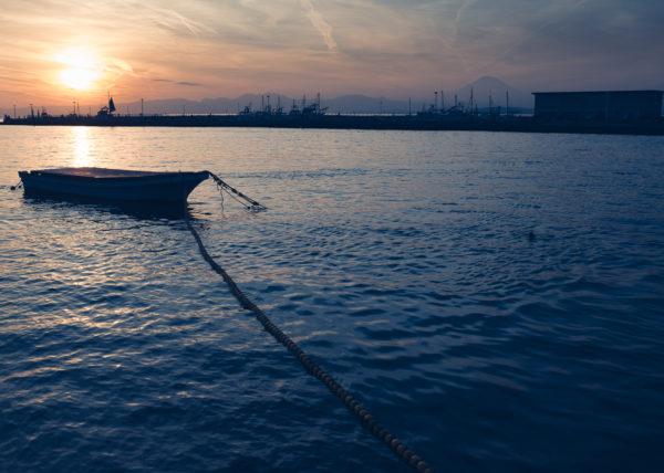 Une barque flotte sur la mer d'Enoshima tandisque le soleil se couche