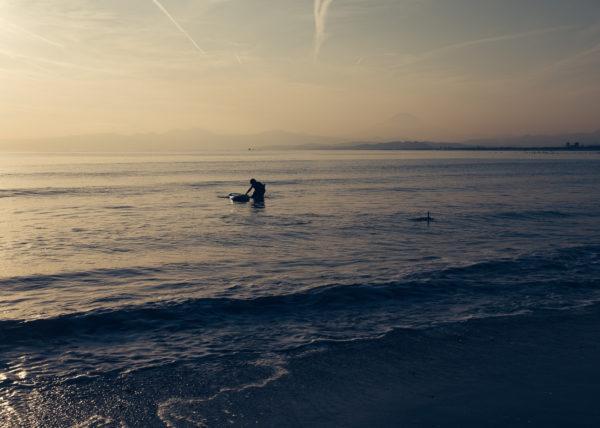 Plus que quelques rayons de soleil éclairent encore la mer et ce surfeur sur la plage d'Enoshima