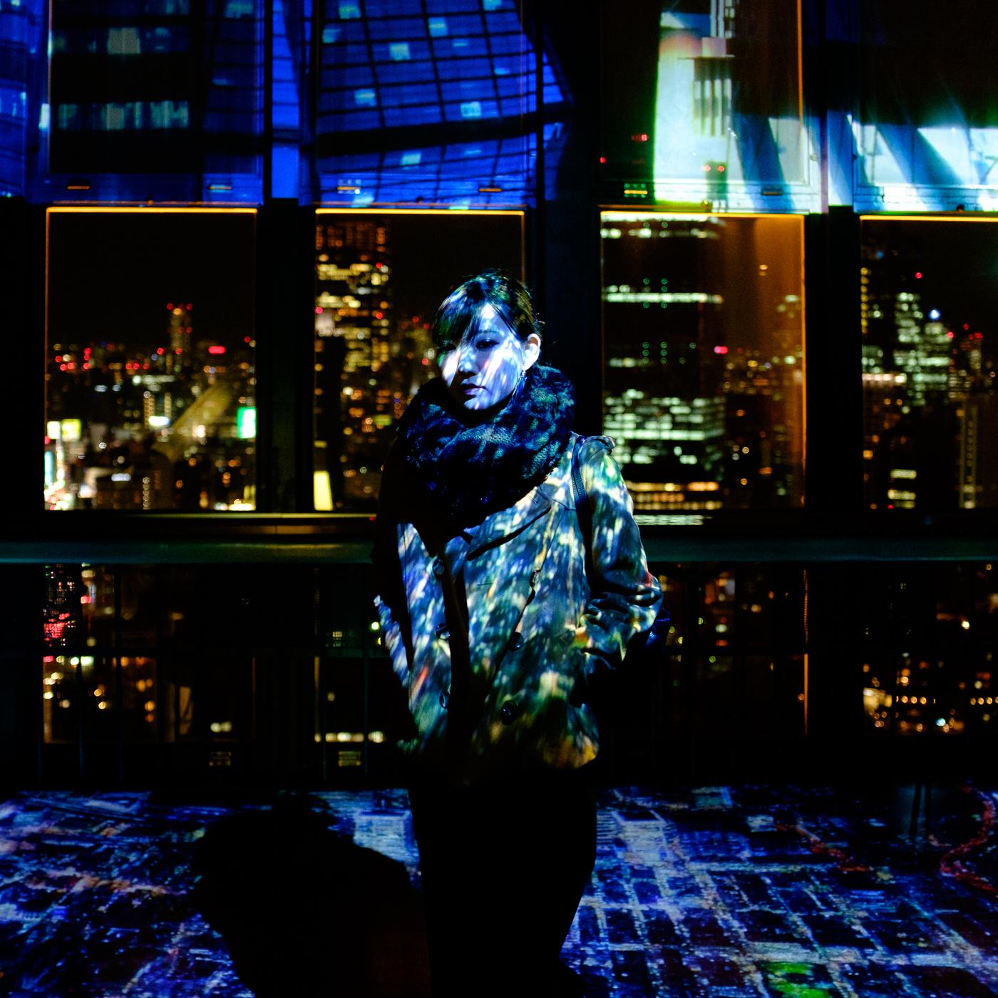 Portrait au sommet de la tour de Tokyo, en pleine nuit, au milieux des lumières de la ville
