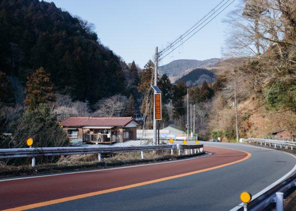 Une petite maison semble bien isolée en bord de route, au milieux des montagnes japonaises