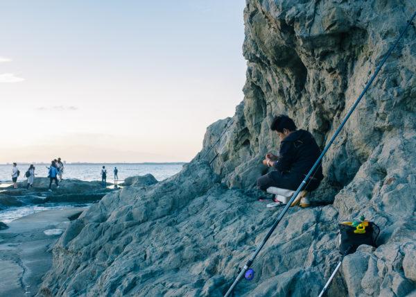 Un pêcheur au creux des rochers se prépare à pêcher dans les aux d'énoshima